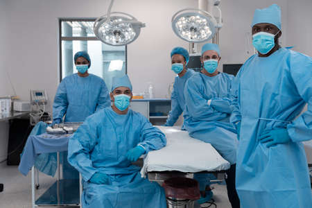 Diverse surgeons wearing face masks and protective clothing in operating theatre. medicine, health and healthcare services during covid 19 coronavirus pandemic. Stockfoto