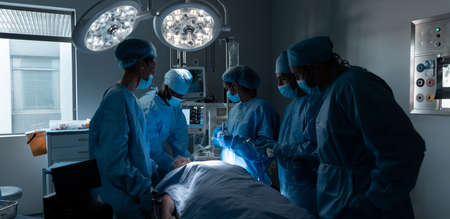 Diverse surgeons with face masks and protective clothing during operation in hospital. operating theatre. medicine, health and healthcare services during covid 19 coronavirus pandemic.