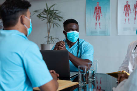 Diverse male and female doctors wearing face masks sitting in hospital having discussion. medicine, health and healthcare services during coronavirus covid 19 pandemic.