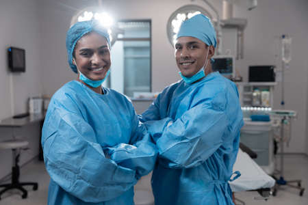 Smiling diverse male female surgeons with face masks and protective clothing in operating theatre. medicine, health and healthcare services during covid 19 coronavirus pandemic. Stockfoto