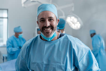 Smiling caucasian male surgeon with face mask and protective clothing in operating theatre. medicine, health and healthcare services during covid 19 coronavirus pandemic.