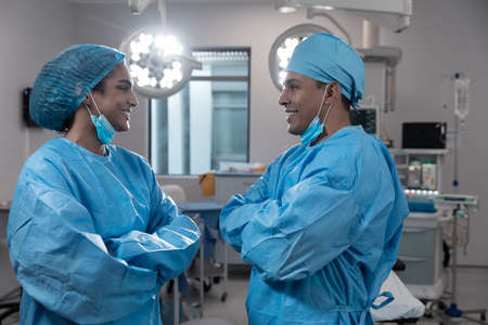 Diverse male and female surgeons wearing face masks and protective clothing in operating theatre. medicine, health and healthcare services during covid 19 coronavirus pandemic.