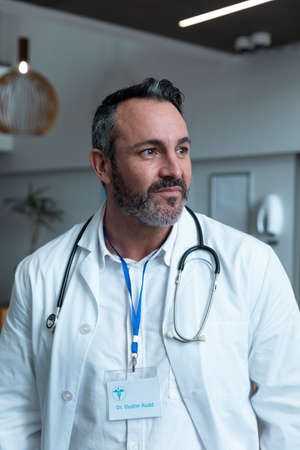 Portrait of caucasian male doctor with stethoscope wearing lab coat in hospital. medicine, health and healthcare services during covid 19 coronavirus pandemic.
