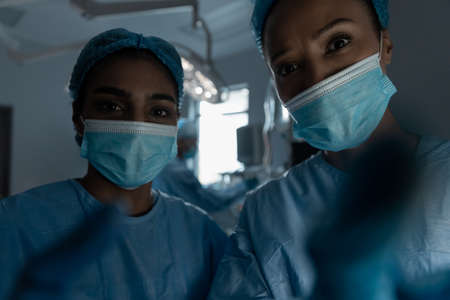 Diverse female doctors wearing face masks and surgical overalls looking at camera. medicine, health and healthcare services during coronavirus covid 19 pandemic.