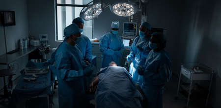 Diverse male and female doctors wearing face masks and surgical overalls in operating theatre. medicine, health and healthcare services during coronavirus covid 19 pandemic. Stockfoto