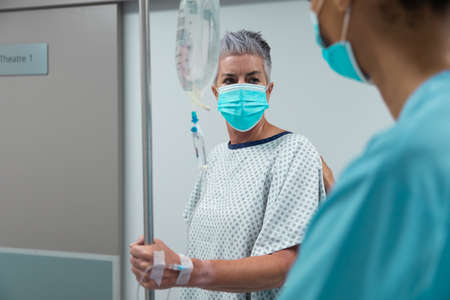 Caucasian female patient wearing face mask standing on corridor with drip bag and talking to doctor. medicine, health and healthcare services during coronavirus covid 19 pandemic. Stockfoto