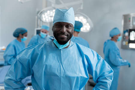 Smiling african american male surgeon with face mask and protective clothing in operating theatre. medicine, health and healthcare services during covid 19 coronavirus pandemic.
