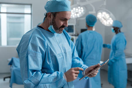Caucasian male surgeon with face mask and protective clothing using tablet in operating theatre. medicine, health and healthcare services during covid 19 coronavirus pandemic. Stockfoto