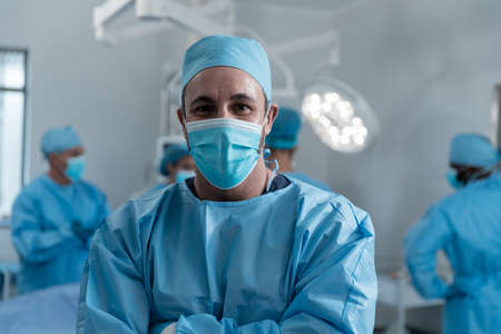 Portrait of caucasian male surgeon wearing face mask and protective clothing in operating theatre. medicine, health and healthcare services during covid 19 coronavirus pandemic. Stockfoto