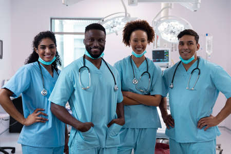 Portrait of smiling diverse surgeons wearing scrubs in operating theatre. medicine, health and healthcare services during covid 19 coronavirus pandemic.
