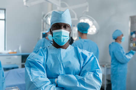 African american male surgeon with face mask and protective clothing in operating theatre. medicine, health and healthcare services during covid 19 coronavirus pandemic.