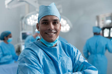 Smiling mixed race male surgeon with face mask and protective clothing in operating theatre. medicine, health and healthcare services during covid 19 coronavirus pandemic. Stockfoto
