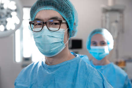 Portrait of mixed race male surgeon standing in operating theatre wearing face mask. medicine, health and healthcare services during coronavirus covid 19 pandemic.