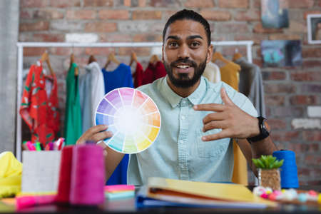 Mixed race male designer in sitting at desk holding a colour chart and smiling. independent creative fashion design business. Stockfoto