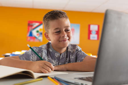 Caucasian boy sitting at a desk in classroom writing, looking at laptop and smiling. childhood, technology and education at elementary school.