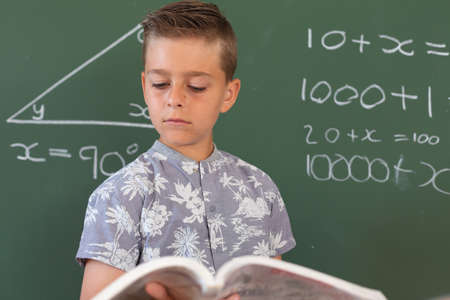 Caucasian boy standing at chalkboard in classroom holding schoolbook during maths lesson. childhood and education at elementary school.