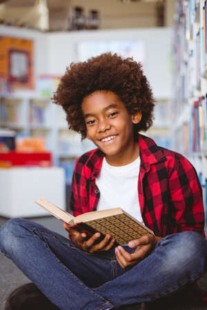 Portrait of smiling african american schoolboy reading book sitting on floor in school library. childhood and education at elementary school. Reklamní fotografie