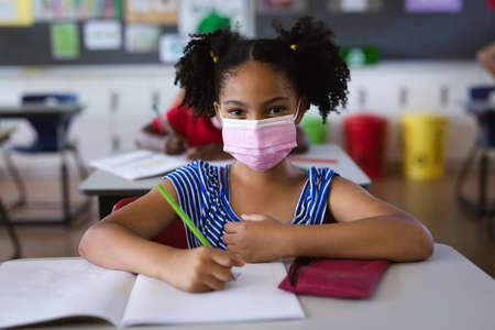 Portrait of african american girl wearing face mask sitting on her desk in the class at school. education back to school health safety during covid19 coronavirus pandemic