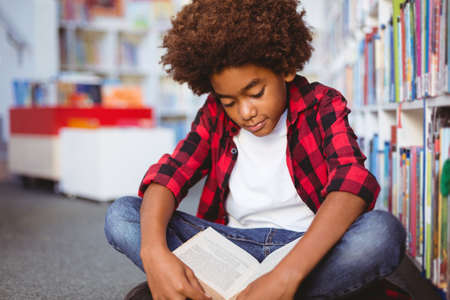 Happy african american schoolboy reading book sitting on floor in school library. childhood and education at elementary school.