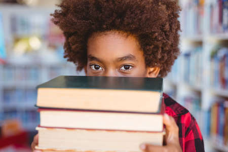 Portrait of african american schoolboy carrying stack of books in school library. childhood and education at elementary school.
