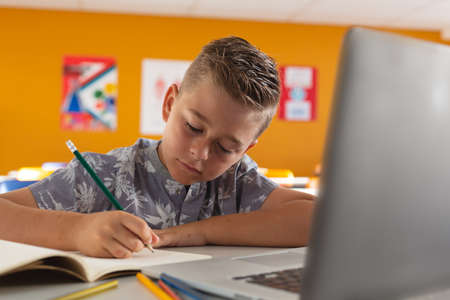 Caucasian boy sitting at a desk in classroom writing and using laptop. childhood, technology and education at elementary school.
