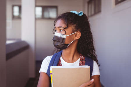 African american schoolgirl in face mask standing in school corridor holding books. childhood and education at elementary school during coronavirus covid19 pandemic.