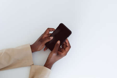 Hand of african american woman holding smartphone with copy space on screen. independent creative business at a modern office. Reklamní fotografie