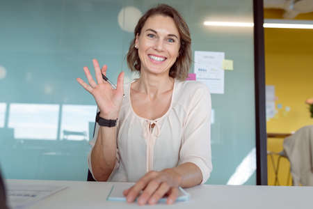 Smiling caucasian businesswoman sitting, having business video call at work. independent creative business at a modern office.