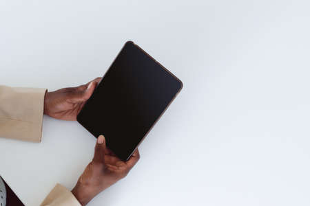 Hand of african american woman holding tablet with copy space on screen. independent creative business at a modern office. Reklamní fotografie