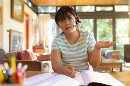 Asian girl wearing phone headset talking during video call, learning online. at home in isolation during quarantine lockdown.
