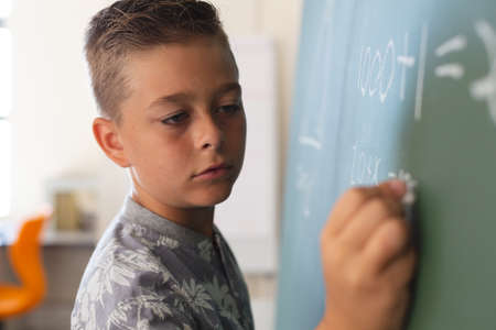 Caucasian boy standing at chalkboard writing in classroom during maths lesson. childhood and education at elementary school.