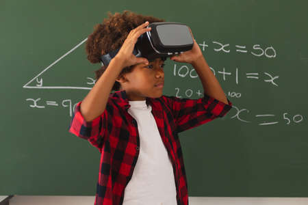 African american schoolboy in front of chalkboard in classroom using vr headset. childhood, technology and education at elementary school.