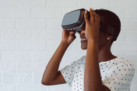 Smiling african american woman using vr headset at work. independent creative business at a modern office. Reklamní fotografie