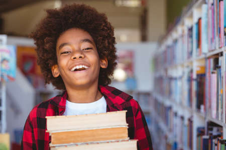 Laughing african american schoolboy carrying stack of books in school library. childhood and education at elementary school. a