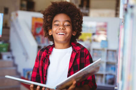 Laughing african american schoolboy reading book standing in school library. childhood and education at elementary school.