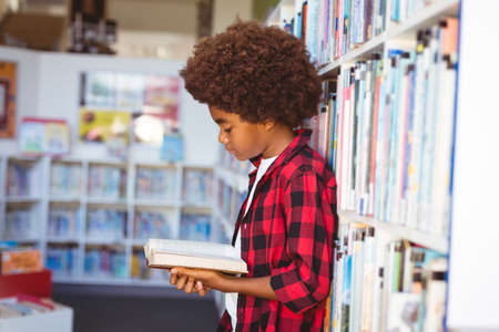 Happy african american schoolboy reading book standing in school library. childhood and education at elementary school.