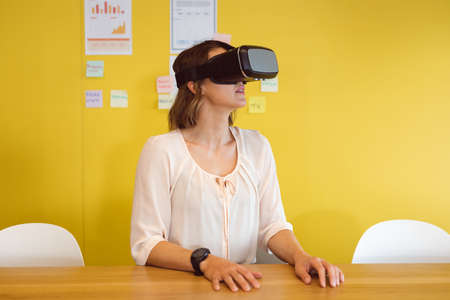 Caucasian woman sitting at desk using vr headset at work. independent creative business at a modern office.
