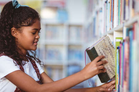 Portrait of happy african american schoolgirl taking book from shelf in school library. childhood and education at elementary school.