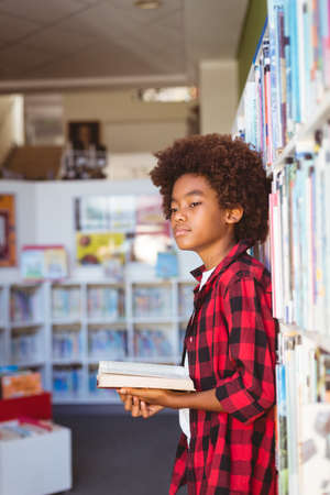 Happy african american schoolboy reading book standing in school library, looking away. childhood and education at elementary school.