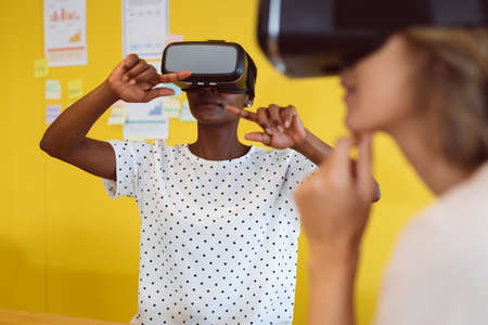 Diverse businesswomen sitting at desk using vr headset at work. independent creative business at a modern office.