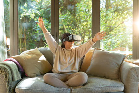 Smiling asian girl wearing vr headset with arms outstretched sitting on sofa. at home in isolation during quarantine lockdown.