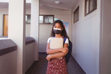 Portrait of african american schoolgirl in face mask standing in school corridor holding books. childhood and education at elementary school during coronavirus covid19 pandemic. Reklamní fotografie