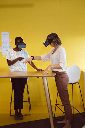 Diverse businesswomen standing at desk using vr headset at work. independent creative business at a modern office. Reklamní fotografie