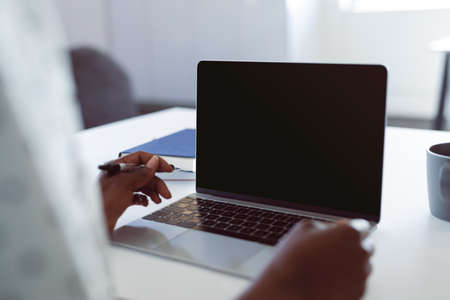 African american woman using laptop with copy space on screen. independent creative business at a modern office.