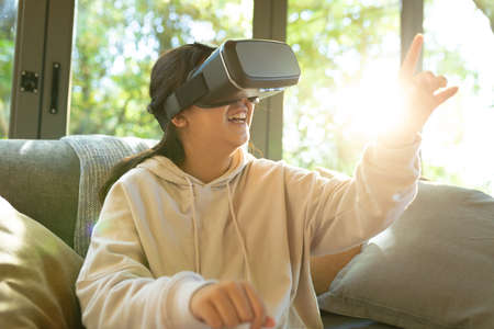 Smiling asian girl wearing vr headset touching with her finger sitting on sofa. at home in isolation during quarantine lockdown.