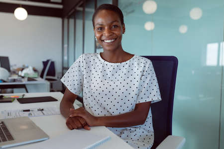Smiling african american businesswoman sitting at desk at work. independent creative business at a modern office.