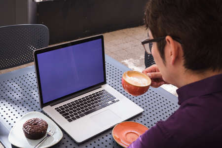 Asian businessman using laptop with blank screen drinking coffee in cafe. digital nomad out and about in city concept. Reklamní fotografie