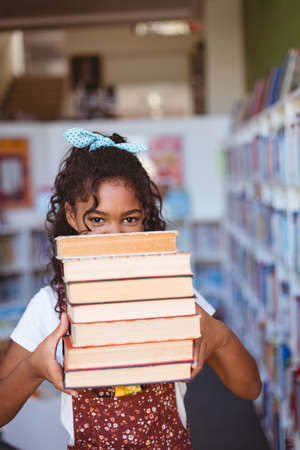 Portrait of happy african american schoolgirl carrying stack of books in school library. childhood and education at elementary school. Reklamní fotografie