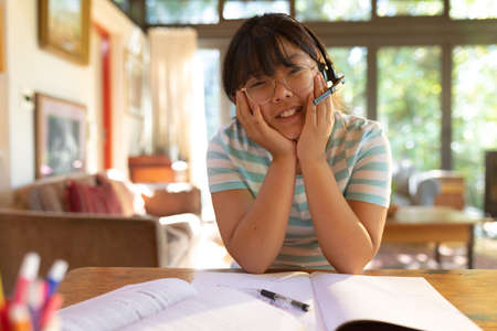 Asian girl wearing phone headset smiling during video call, learning online. at home in isolation during quarantine lockdown.