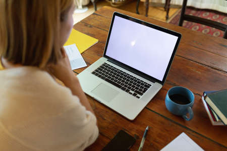 Asian woman on video call using laptop with blank screen, sitting at table, working from home. at home in isolation during quarantine lockdown.
